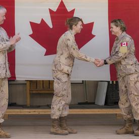 La gouverneure générale Julie Payette serre la main d'un membre des Forces armées canadiennes.