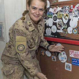 La gouverneure générale Julie Payette appose un autocollant de ses armoiries sur un mur.