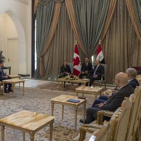 Governor General Julie Payette and His Excellency Barham Salih, President of Iraq are speaking to each other. An interpreter is sitting between them. Canadian and Irak officials are sitting on either side of the room.