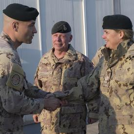 Governor General Payette shakes hands with a CAF member. General Jonathan Vance, Chief of the Defence Staff, is standing beside her.