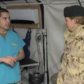Governor General Julie Payette talks to a CAF member in medical gear.