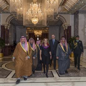 La gouverneure générale Julie Payette marche dans la palais Bayan entourée d'hommes Koweïtiens.