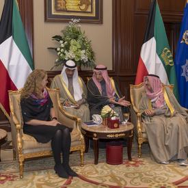 La gouverneure générale Julie Payette est assise avec trois hommes koweïtiens. Des drapeaux colorés sont derrière eux.