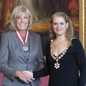 La gouverneure générale serre la main de Sally Wishart Armstrong.  Tous deux portent l'insigne de l'Ordre du Canada.