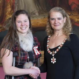 La gouverneure générale serre la main de Stephanie Dixon.  Tous deux portent l'insigne de l'Ordre du Canada.