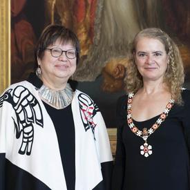 La gouverneure générale se tient aux côtés de Judith Sayers.  Tous deux portent l'insigne de l'Ordre du Canada.