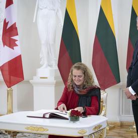 La gouverneure générale a signé le livre d'or présidentiel.