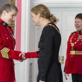 Diane L. Cockle serre la main de la gouverneure générale.  Derrière eux, à droite, la commissaire de la GRC, Brenda Lucki.  Tous les trois portent leur insigne.