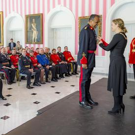Satpal Singh Parhar receives his insignia from the Governor General.  RCMP Commissioner Brenda Lucki observes them standing behind them to the right.  All three are standing on stage in front of a room filled with people.