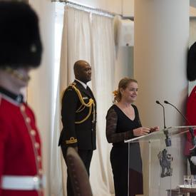 La gouverneure générale prend la parole devant un podium et prononce un discours.  De chaque côté d'elle se trouvent des gardes de cérémonie.  Derrière elle, il y a son aide de camp.