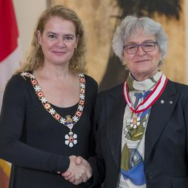 Louise Nadeau se tient à côté de la Gouverneure générale.  Tous deux sourient à la caméra.  Elles portent leur insigne de l'Ordre du Canada.