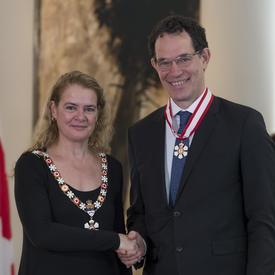 Neil G. Turok  se tient à côté de la Gouverneure générale.  Tous deux sourient à la caméra.  Ils portent leur insigne de l'Ordre du Canada.