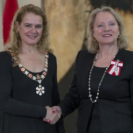 Agnes Di Leonardi se tient à côté de la Gouverneure générale.  Tous deux sourient à la caméra.  Elles portent leur insigne de l'Ordre du Canada.
