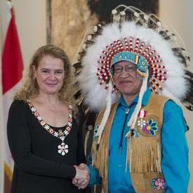 Edmund Metatawabin se tient à côté de la Gouverneure générale.  Tous deux sourient à la caméra.  Ils portent leur insigne de l'Ordre du Canada.