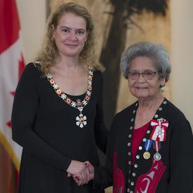 Marjorie White se tient à côté de la Gouverneure générale.  Tous deux sourient à la caméra.  Elles portent leur insigne de l'Ordre du Canada.