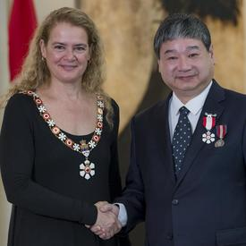 Yiyan Wu se tient à côté de la Gouverneure générale.  Tous deux sourient à la caméra.  Ils portent leur insigne de l'Ordre du Canada.