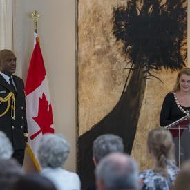 La gouverneure générale se tient derrière un podium et fait face à une salle pleine de gens.  Elle prononce un discours.