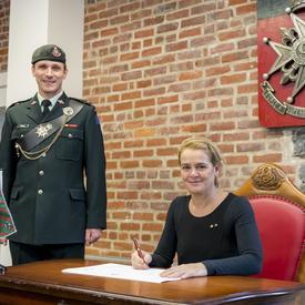 La gouverneure générale Julie Payette regarde directement le photographe, alors qu'elle est assise à une table, stylo à la main, prête à signer un document. Un homme en uniforme se tient à sa droite.