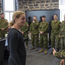 La gouverneure générale Julie Payette écoute une femme en uniforme de combat. A côté de la femme, d'autres personnes portant l'uniforme sont alignées, attendant aussi de lui parler.