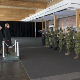 La gouverneure générale Julie Payette est debout sur un dais et regarde une garde de caserne composée de deux rangées de huit réservistes en uniforme de combat.