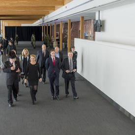 La gouverneure générale Julie Payette, accompagnée d'un groupe d'une dizaine de personnes, marche dans le hall d'entrée du Manège militaire des Voltigeurs de Québec.