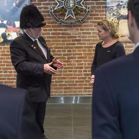 Un homme en complet et portant un chapeau à plumes noires s'adresse à la gouverneure générale qui l'écoute attentivement.