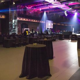 Plan très large d'une grande salle sombre avec une scène éclairée sur laquelle une chanteuse est en répétition.