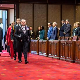 The Governor General, led by the Usher of the Black Rod, enters the Senate Chamber.