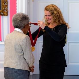 La gouverneure générale remet une médaille à Sylvia D. Hamilton.