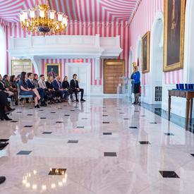 Vue latérale de Mme Assunta Di Lorenzo s'adressant à un public, depuis un podium, dans la salle de la tente rouge, noire et blanche de Rideau Hall.