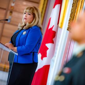 Vue latérale de Mme Assunta Di Lorenzo s'adressant à un public, depuis un podium. Un drapeau canadien est derrière elle.