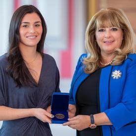 gauche, une étudiante universitaire aux cheveux noirs tient une boîte bleue ouverte contenant une médaille. Une femme blonde portant une veste bleue se trouve à droite.