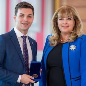 À gauche, un étudiant universitaire de sexe masculin portant une veste bleue tient une boîte bleue ouverte contenant une médaille. À droite, une femme blonde portant une veste bleue.