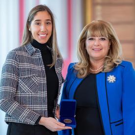 À gauche, une grande étudiante universitaire tient une boîte bleue ouverte contenant une médaille. Une femme blonde portant une veste bleue se trouve à droite.
