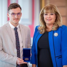À gauche, un étudiant universitaire portant une veste gris clair tient une boîte bleue ouverte contenant une médaille. À droite, une femme blonde portant une veste bleue.