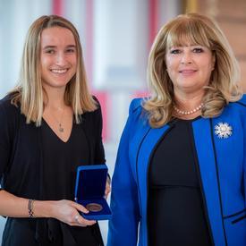 À gauche, une étudiante universitaire blonde tient une boîte bleue ouverte contenant une médaille. À droite, une femme blonde portant une veste bleue.