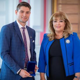 À gauche, un étudiant universitaire de sexe masculin portant une veste bleue tient une boîte bleue ouverte contenant une médaille. Une femme blonde portant une veste bleue se trouve à droite.