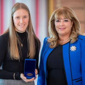 On the left, a blond female university student is holding an opened blue box containing a medal. A blond woman wearing a blue jacket is on the right.