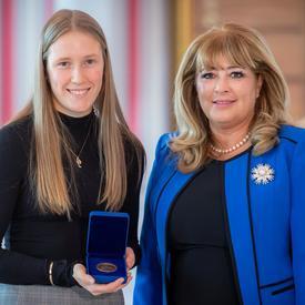 gauche, une étudiante universitaire blonde tient une boîte bleue ouverte contenant une médaille. Une femme blonde portant une veste bleue se trouve à droite.