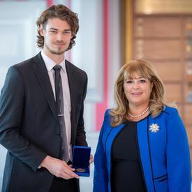 À gauche, un grand étudiant universitaire tient une boîte bleue ouverte contenant une médaille. Une femme blonde portant une veste bleue se trouve à droite.