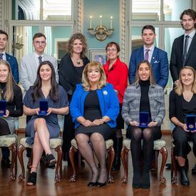 Un groupe de personnes pose pour la photo. La première rangée de personnes est assise. Les personnes derrière sont debout.