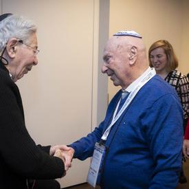 Two Holocaust survivors shake hands.