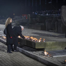 The Governor General places a lite candle at the monument.
