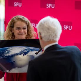 The Governor General presents the President of Simon Fraser University with a photo of Vancouver taken from space.