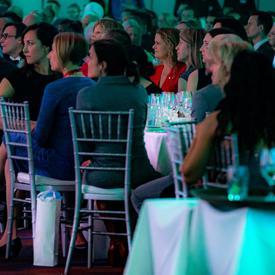 La gouverneure générale s'assoit à une table avec des invités lors d'un gala.