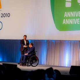 Alexandre Bilodeau delivers remarks with his brother on stage.