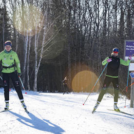 Competitive cross-country skiers racing down a trail.