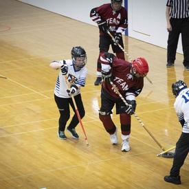 Des athlètes des Jeux olympiques spéciaux sur le terrain lors d'une partie de hockey intérieur.