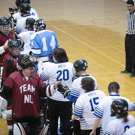 Deux équipes s'alignent pour se serrer la main après un match compétitif.
