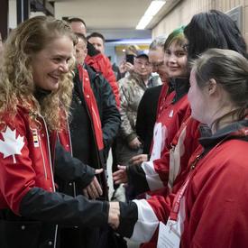 Vêtu de rouge Canada, la gouverneure générale serre la main des athlètes des Jeux olympiques spéciaux après leur match.